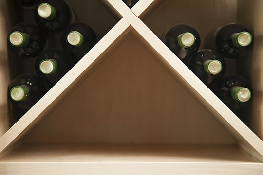 Bottles of wine neatly stored on a on a wine rack